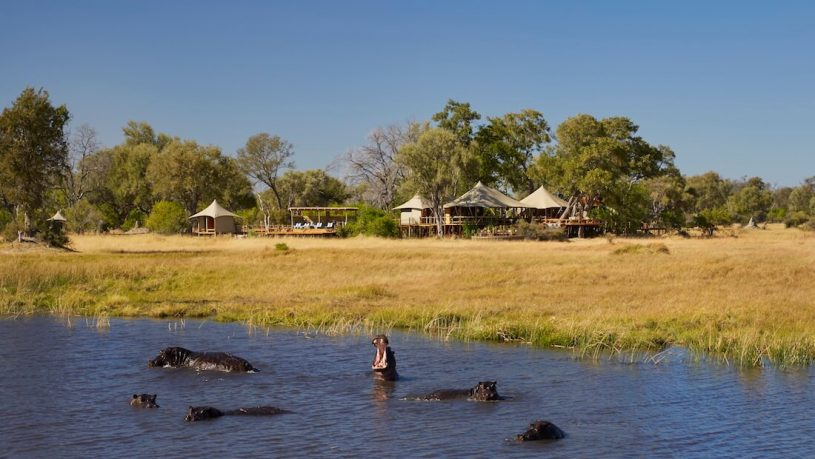 Tuludi Camp exterior and hippos in the lagoon